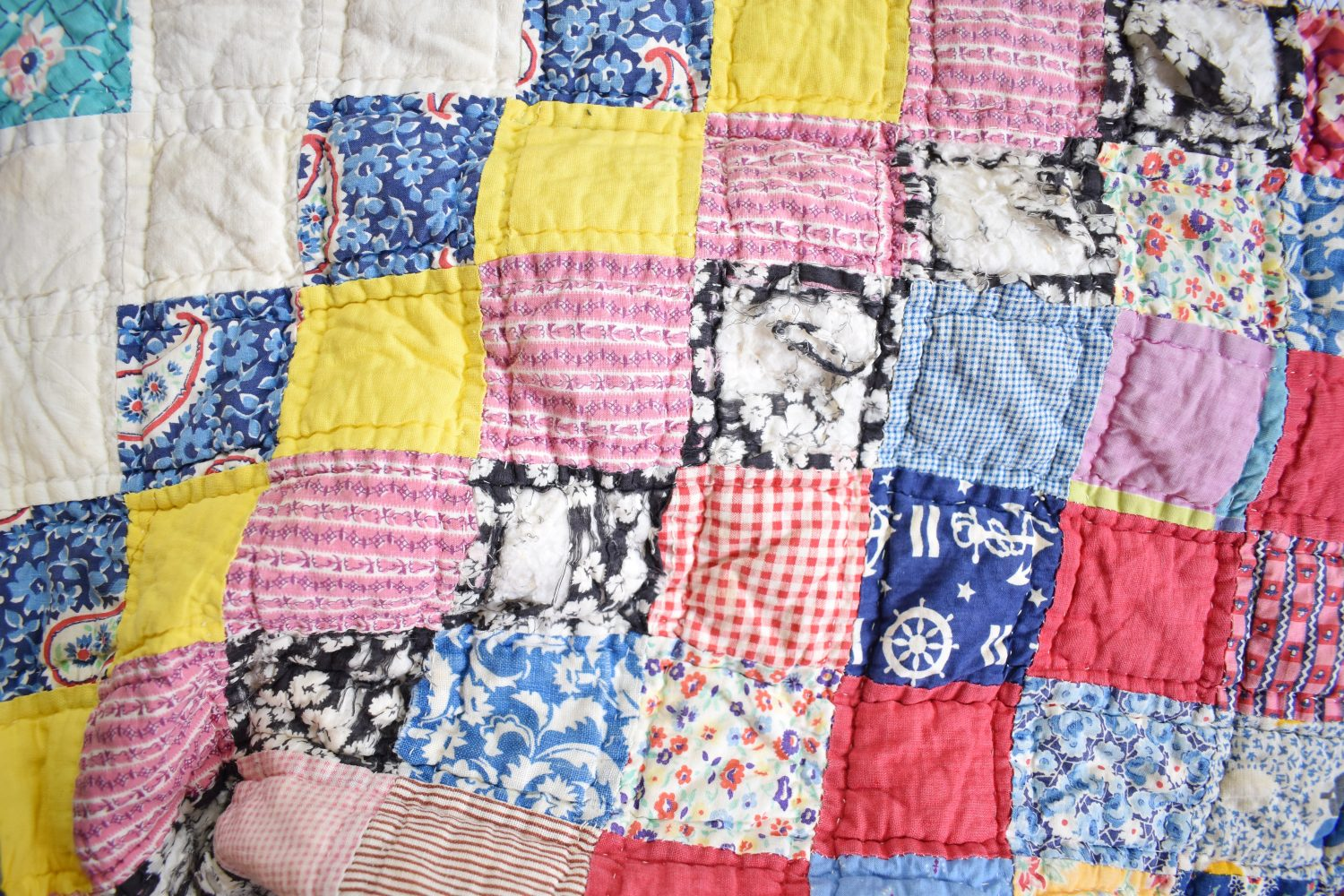 Fabric tears that need mending on a vintage quilt